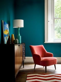 Teal walls and red statement chair