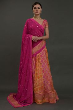 From our Bridal Heritage Collection, this orange-hot pink ombre lehenga outfit brings together the beauty of handwoven Banarasi zari craft and iconic Gujarati bandhej. The pure georgette lehenga and crop top has all over handcrafted mustard-white Pakistani Bridal Wear, Bridal Lehenga Choli, Indian Lehenga, Designer Dress For Men, Indian Designer Wear, Designer Dresses, Lehenga Crop Top, Lehenga Skirt, Indian Wedding Outfits