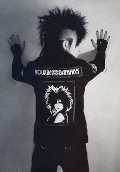 [B/w photo of a person in a hand-decorated jacket with Siouxsie and the Banshees patches]