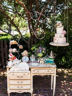 This whimsical Alice In Wonderland wedding cake display is even better than imagined. Vintage glam tea sets fashioned alongside delightful pastel desserts make for the tea party of your dreams.