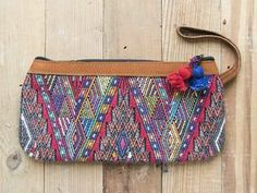 """$48.00   Colorful woven wristlet pouch in """"volcano"""" pattern. This one of a kind piece is made using recycled blouses of indigenous Central and South American women and trimmed in leather along the top and wrist strap.   Your purchase allows women in Central and South America consistent work and fair trade wages that would otherwise have no means of income or way to support their families."""