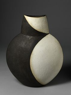John Ward begins by coil-building his pots, and then cuts and rejoins the curved surfaces to create more angular shapes. The black and white glazes on this flattened pot exaggerate its curves by suggesting the idea of a shadow
