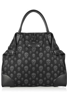 Black nylon tote bag with burnished-silver hardware. Alexander McQueen tote has two top leather handles, a zip fastening at top, a designer-stamped leather plaque at front with studs, leather detailing on lower corners, magnetic disks to create fold-over corners at top, leather feet on base, an internal zipped pocket and is fully lined.