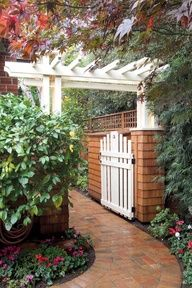 An exceptionally handsome brick walk leads through a picket-fence garden gate; the red brick and red cedar are a nice pairing.