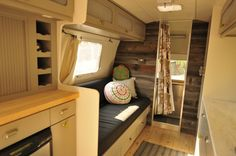 The wood wall gives the tiny interior of this airstream a rustic charm. The gray cabinets and dark cushions are a combination with the paneled wall.