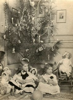 1916 Christmas tree, with children with their new dolls. One chides holding a Belsnickle Santa. On the floor is a cast iron Teddy Roosevelt bank.