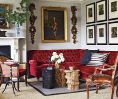 This drawing room has a decidedly dramatic take on English decor. A bold, tufted red velvet sofa and 18th century English portrait hung in a gilded frame make for a sumptuous, stately space. A regency chair, leather armchair and Georgian wood garlands lend an air of tradition and masculinity.