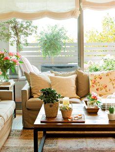 Salón con vistas a la terraza, sofá con cojines, mesa de centro en madera y metal, estores blancos y flores