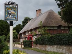 Archetypal English Village with a sign for the local, Tichborne Arms, and the village post office with a thatched roof