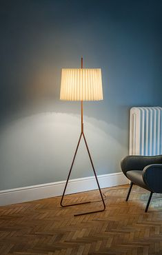 Julius T. Kalmar originally conceived the floor lampFliegenbein in 1957, as a pairing of slender and voluminous shapes that complement any modern living environment. The freestanding armature comprises two bent metal tubes that merge into a single shaft, anda pleated silken shade suspends near the top of this column.Three matte finishes accentuatethe shape of the legs, which also featureKalmar Werkstätten's signature wheat-colored electrical cord.