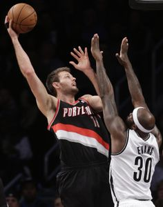 Portland Trail Blazers center Joel Freeland (19) shoots over the defense of Brooklyn Nets power forward Reggie Evans (30) in the first half of their their NBA basketball game at the Barclays Center, Monday, Nov. 18, 2013, in Brooklyn. (AP Photo/Kathy Willens)