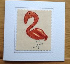 This beautiful heart flamingo were made by sewing metallic copper fabric onto a canvas background. The finished result is similar to that of a painted picture but far more special and unique. The needle was my pen and the fabric was my paint. This card would shine out from any others in a line up. It would be perfect for framing as a special memento to keep long after the event. Each card is individually handmade by me in my studio so small variations from the one in the photo make it…