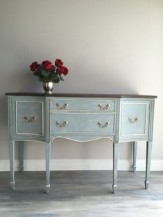 Reloved, refurbished vintage dining room buffet or sideboard. I take an old, well made piece of furniture and make it new. I make all the necessary repairs. Then painted it using Annie Sloan Duck Egg Blue, Paris Grey, French Linen and Old White using a layering technique. I stained the top with three different colors as well. I stained it using gray, ebony and dark walnut to give it depth and dimension. I decoupaged a bird print on the inside of the doors and bottom of the drawers. I added…
