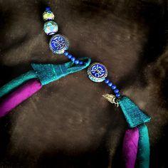 De mi colección de adornos de pluma de ruta de la seda: los toques de esmalte púrpura y azul en esta reproducción contemporánea de un candado chino destacan por el color turquesa brillante y seda púrpura doble-cordones que forman el collar. El lazo que sujeta que la cerradura es antiguo bordado chino - oh, esas puntadas delicadas! Este collares cierra con esmalte botones de bolas chinas en una cadena de lapis, dos botones para darle una longitud ajustable.