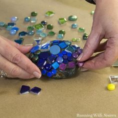 Make colorful mosaic garden rocks using a mix of tiles. We'll show you how to mix and tint the grout with a tutorial video! Garden art How To Make Mosaic Garden Rocks - Running With Sisters Mosaic Garden Art, Mosaic Tile Art, Mosaic Flower Pots, Mosaic Crafts, Mosaic Projects, Mosaic Mirrors, Art Projects, Mosaic Ideas, Garden Projects