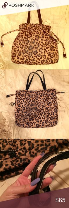 """MK Leopard Tote Authentic Michael Kors quilted nylon leopard drawstring tote! Has silver hardware. I used this bag during all 3 years of law school & LOVED it.  It does show wear! Discoloration from denim on front & back, some stains inside (hard to tell since its black), as well as wear on the straps.   That being said, it has life left! Please see additional pics in 2nd post (bottom of my closet). Definitely not trying to deceive anyone about its condition. ❤️  Approx Measurements: L: 17""""…"""