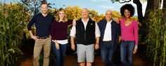 The hosts of the daytime cooking show The Chew stand on a farm surrounded by tall trees and plants
