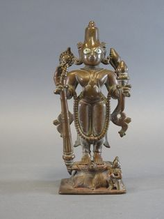 Lot 132 - A BRONZE FIGURE OF VISHNU South India, 18th century the four armed deity standing erect on a