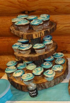 Rustic, outdoor wedding wooden-log cupcake stand. Malibu blue frosted carrot cupcakes.