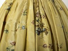 The dress is made of yellow silk taffeta, which is brocaded. This means that the flower design is not embroidered, but woven into the fabric. The skirt of this gown is attached to the bodice at the back and side, the front part of the skirt is held up by strings tied around the waist.  1743-1750  Materials: silk; linen