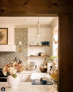 I really love the plain flat white boards that highlight the wood shelves and their display. I also love a white range hood and not sure if it is tile or wallpaper but I really like the cement tile feel, very warm and welcoming kitchen. Kitchen Vent Hood, Cottage Kitchens, Dream Kitchens, Antique Beds, Kitchen Wallpaper, Boho Kitchen, Farmhouse Plans, Wood Shelves, Built Ins