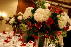 Tall centerpieces surrounded the stage on top of tall rectangle vases filled with white hydrangeas, heat red roses, belles of ireland, red mikado spray roses, red hypericum berries, red kangaroo paws, safari sunset, etc