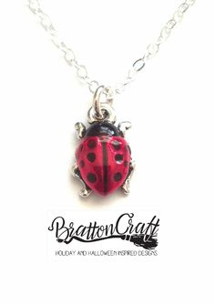Hand Painted Red Ladybug Necklace.   The charm is made in the USA using lead-free Britannia pewter with a nickel compliant fine silver double plating. The charm is approximately 1/2 inches long and 3/8 inches wide. Kimberly hand painted the ladybugs using a nontoxic epoxy resin made with organic compounds.