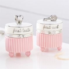 """2-piece set. Fluted ceramic 'first tooth"""" and 'first curl' hinged keepsake boxes feature silver clasp details and platinum ?hand-painted dimensional ?tooth and hairbrush toppers."""