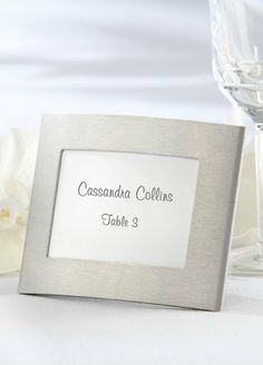 """David's Bridal Silver Photo Frame/Placeholder Style 14014NA by Smart Marketing. $0.84. Elegantly brushed metal curves gently around your guest's name and table number. The soft bend of this unique frame catches the candlelight at your reception, and later serves as a photo frame for your guest's 3"""" x 2"""" photographs. A useful, eye-catching favor!"""