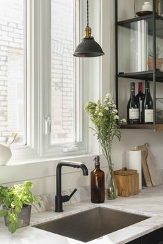 The countertop is Portuguese marble. A Purist faucet from Kohler also features a black matte finish. The pendant lights are vintage glass models, painted in black.