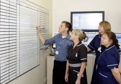 Doctors and nurses at wall chart in Hinchingbrooke NHS Trust