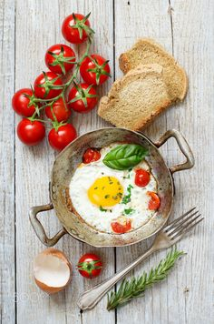 Fried egg on an old frying pan - Fried egg with tomatoes, homemade bread and herbs on a old frying pan on wood
