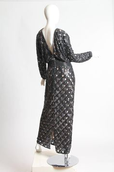 Bob Mackie Beaded Sequin Paillette Gown 1970s or 1980s. Made in gunmetal and black, its dark sheen is sophisticated and glamorous. The gown is cut in a kimono-like silhouette, with a straight skirt, wrap-fronted bodice, deep-V back, and wide sleeves cut in one with the torso.