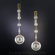 1 and 1/2 inches long, lustrous and lovely! A sparkling white pair of matching old mine-cut diamonds, each weighing approximately 1 carat, float inside gleaming circular frames composed of bright polished platinum over 18K rosy yellow gold, and swing freely from a gently graduated row of small bezel set old-mine diamonds in these sizzling and sexy Edwardian/early Art Deco ear drops dating back to the beginning of the last century. Rare and ravishing originals.