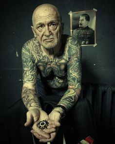 Old guy displaying his lifetime of tattoos.  He looks alright to me but I'm really not into having a whole body covered in tattoos.
