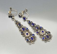 Dramatic and elegant 2 inch long Austro Hungarian chandelier earrings feature a silver filigree pendant with bezel set simulated sapphires with the center surrounded by a ring of delicate seed pea Diamond Drop Earrings, Sapphire Earrings, Gemstone Earrings, Silver Earrings, Pearl Earrings, Sapphire Jewelry, Antique Jewellery Online, Antique Jewelry, Vintage Jewelry
