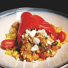 Stuffed red pepper with couscous, zucchini, squash, corn and garlic. topped with feta cheese.