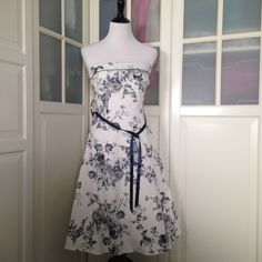 Off white and navy floral dress Simply adorable off white color and navy floral dress. Has a navy ribbon. About knee length to tea length depending on height. Size 9 but my mannequin is a 6-8 for reference. Never worn. Teeze me Dresses
