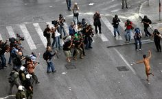 A naked protestor runs during clashes in front of parliament in Athens on October 9, 2012. (Dimitri Messinis/Associated Press) #
