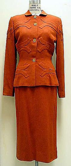Suit  Gilbert Adrian  (American, 1903–1959)    Date:      ca. 1944  Culture:      American  Medium:      (a, b) wool  Dimensions:      Length at CB (a): 25 1/8 in. (63.8 cm) Length at CB (b): 31 in. (78.7 cm)  Credit Line:      Gift of Jones Apparel Group, U.S.A., 2002  Accession Number:      2002.326.2a, b    This artwork is not on display
