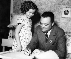 Here in 1937, J. Edgar Hoover is apparently being made a member of the Shirley Temple Police Force.