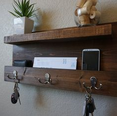 Handmade entryway shelf mail organizer with satin nickel finish hooks. Perfect for any home entryway, apartment, or condo. Made from solid wood. It has been lightly sanded down, then stained and sealed with a beautiful dark walnut finish. This piece does not include the accessory items as shown in the pictures. The color of the stained wood captured in the photos might vary slightly. Dimensions: 23 in wide x 11 in tall x 4 in deep (pocket slot 1.5 in deep, top shelf 3.5 in deep x 21 in lo...