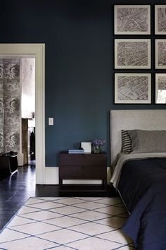Dark real walls, love the masculine geometric pictures above the headboard