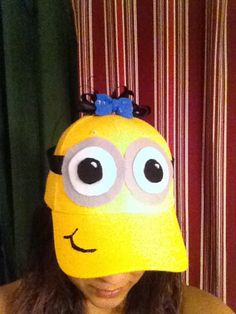 My minion hat!! Easy and super cute!! Grey, white, and black felt circles for the eyes. Black ribbon for the straps, and a little puffy paint for mouth. Black ribbon for hair and plastic blue now glued on top!!