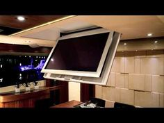 Television mounted on a ceiling hinge on a yacht. The TV is hidden in the ceiling when not in use, then hinges down on command to the desired viewing angle. Tv Ceiling Mount, Ceiling Tv, Tv Wall Design, House Design, Tv Escondida, Tv Stand Room Divider, Swivel Tv Stand, Hidden Tv, Tv In Bedroom