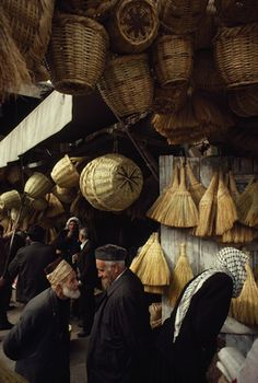 Straw brooms and reed baskets await buyers at a bazaar in Damascus. by James L. Stanfield