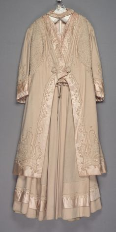 Walking suit: coat and skirt Date: 1907 Media: Wool Broadcloth, Satin, And Soutache Accession Number: 56.35.18a-b Walking suit of cream wool broadcloth: (a) jacket; cutaway front with pleated satin-bound waistcoat and back standing collar; upper part of coat trimmed with soutache embroidery front and back; sleeves shirred at shoulders with three inch wide satin band around wide sleeve ends finished with one and a half inch wide satin ruffle.