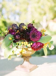 Gorgeous dahlia urn centerpiece - perfect for mid-season weddings, September between summer and fall. Burgundy, green, purple, eggplant flowers, berries and artichokes.