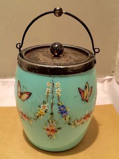 This listing is for a gorgeous Bristol glass biscuit jar with silver plate handle , lid and rim . It is beautifully hand decorated butterflies and flower festoons on a baby blue background .