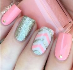Pink nails with gold round studs, silver glitter accent nail and pink and silver chevrons on middle